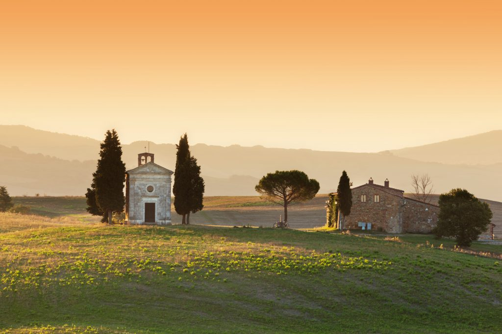 Small chapel in a field at sunset flanked by two cypresses | Tuscan red wines | Tuscan Wanders travel blog