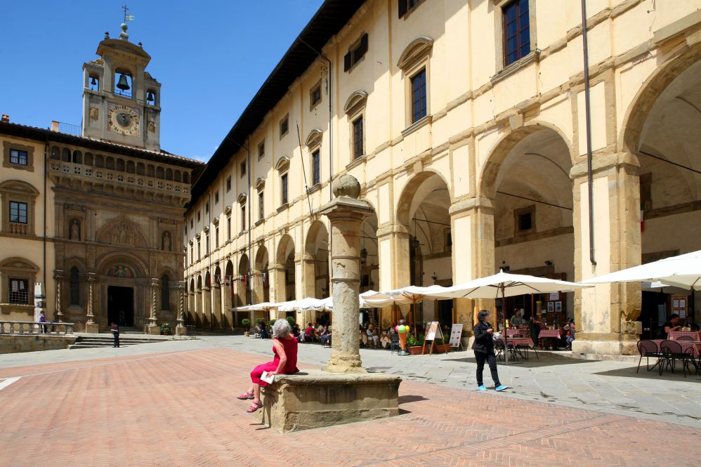 Central piazza of Arezzo surrounded by porticos in a sunny day
