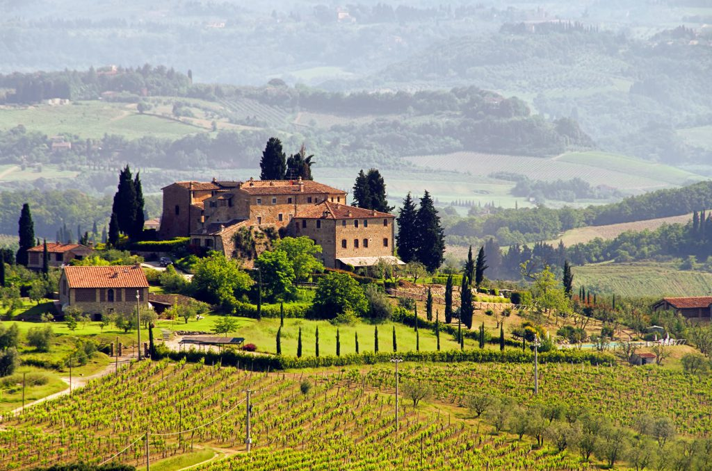 An ancient Tuscan villa in the countryside surrounded by trees and vineyards   Tuscan red wines   Tuscan Wanders Travel Blog