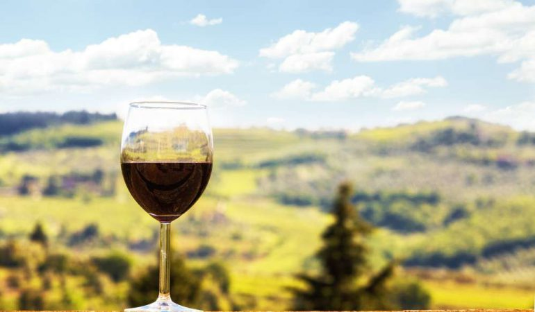 A glass of Chianti classico wine on a Chiantishire landscape