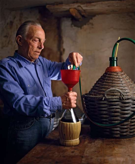 Man pouring wine into the typical Chianti wine flask | What is Chianti classico