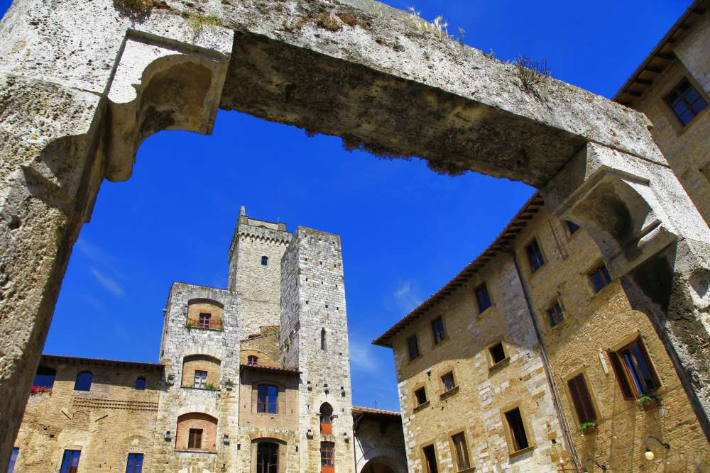 The towers of San Gimignano as seen through the well in Piazza della Cisterna   Things to do in San Gimignano
