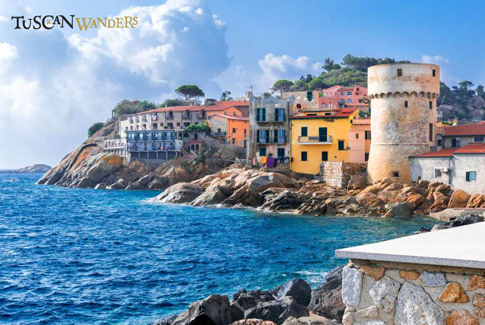 Coloured houses on rocky seaside with a medieval tower on Isola del Giglio