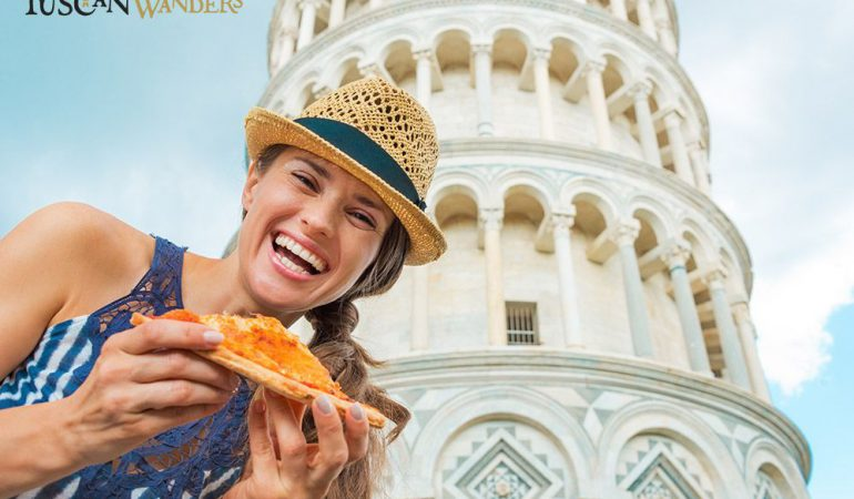 A smiling girl, a slice of Pizza and the leaning tower in a sunny day: can you imagine something more Italian?