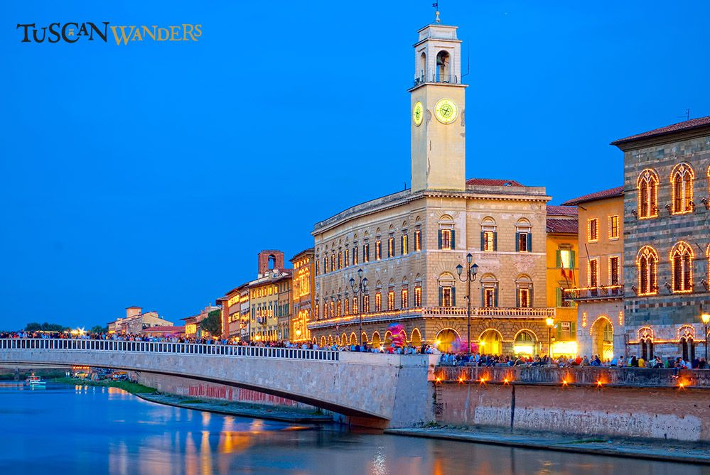 A night view of Pisa with a bridge and the Arno river