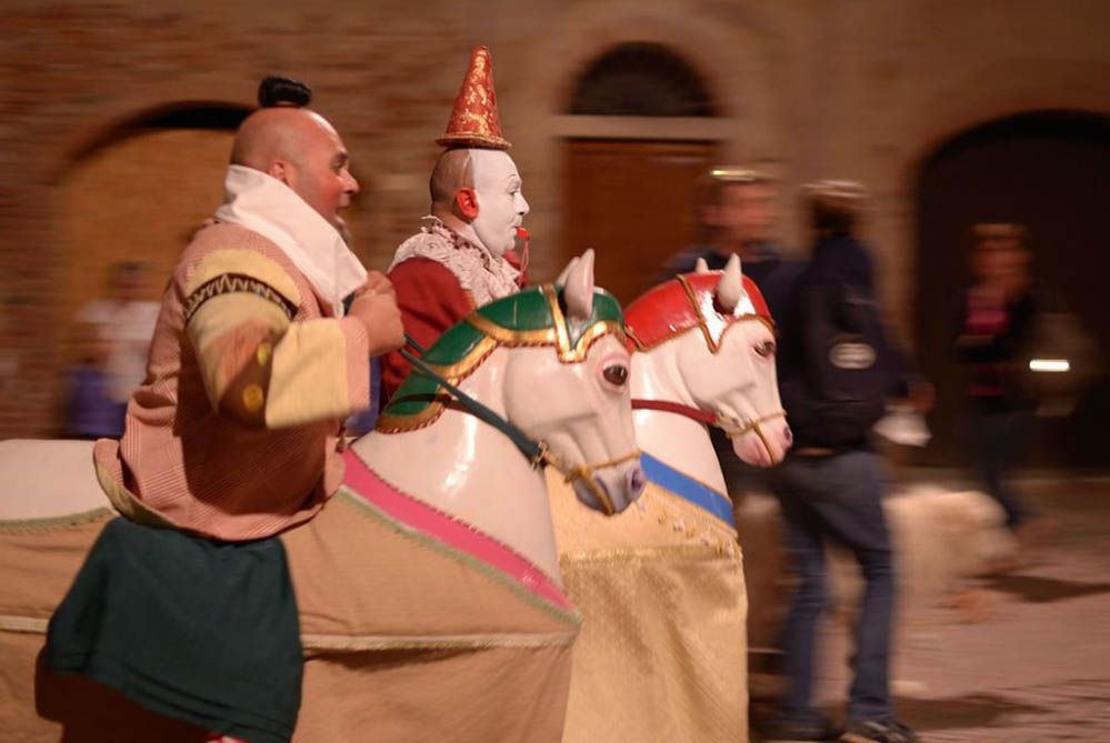 Two masked people running on fake horses