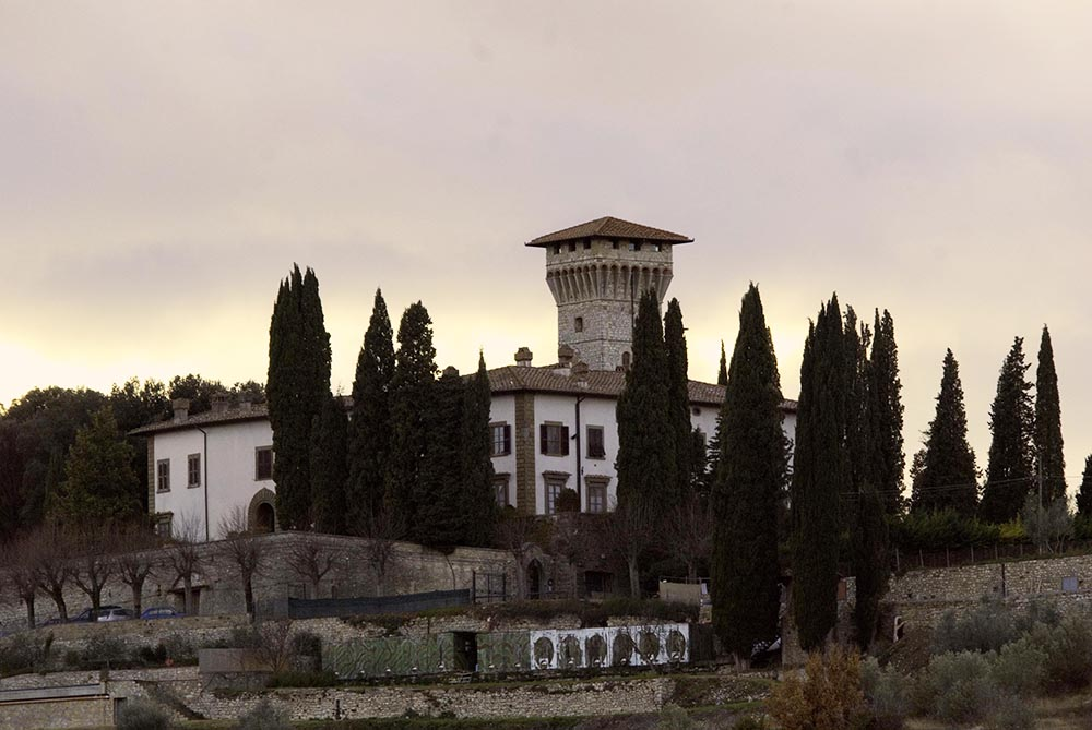 Vicchiomaggio Castle seen from a distance and surrounded by cypresses