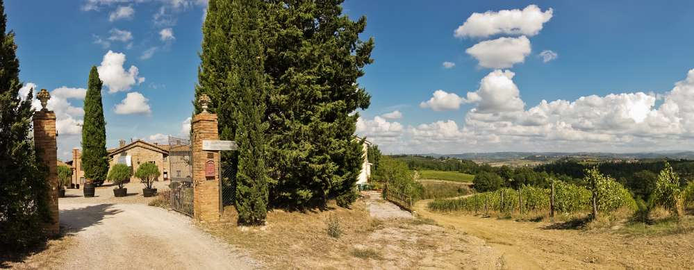 Gate of a Tuscan building with cypresses and hills landscape