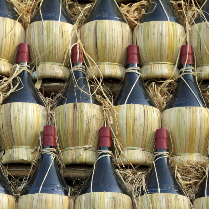 Chianti bottles with straw basket lined up for transportation