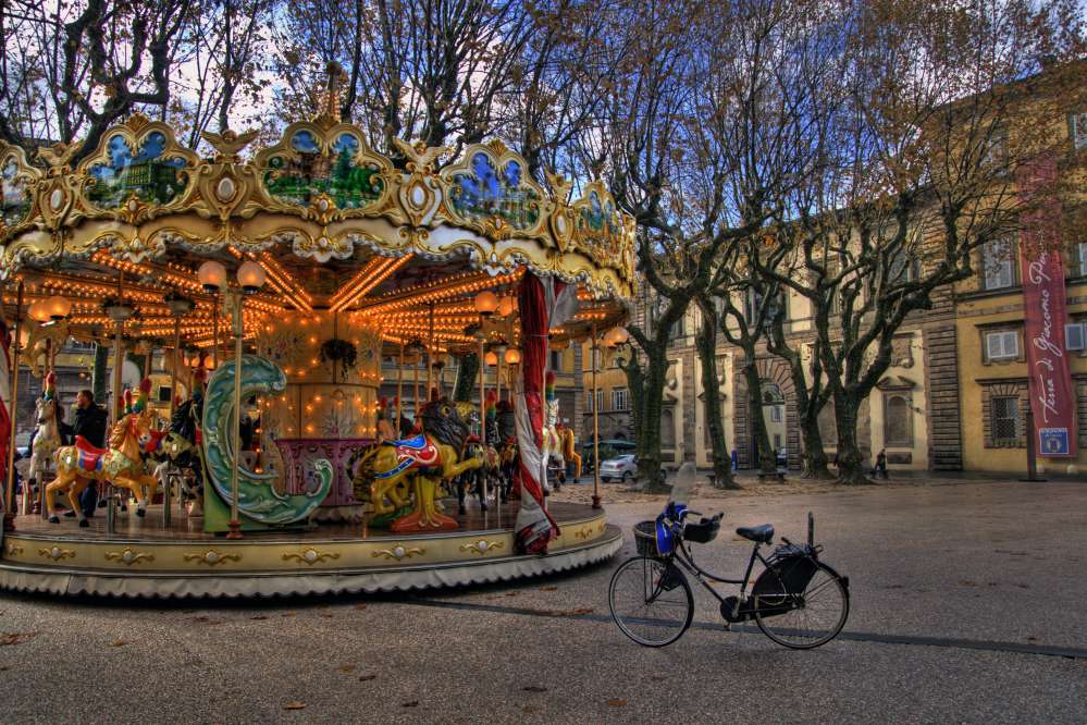 Carousel in piazza Napoleone, Lucca, with bicycle with leafless trees during winter season