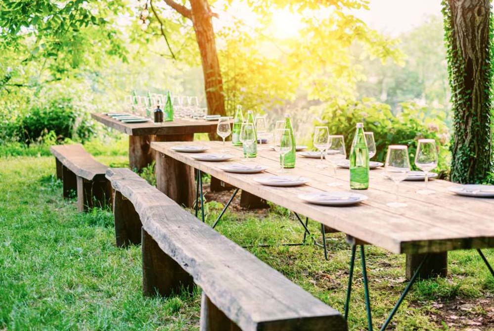 A wooden table dressed in the garden with dishes, glasses and bottles