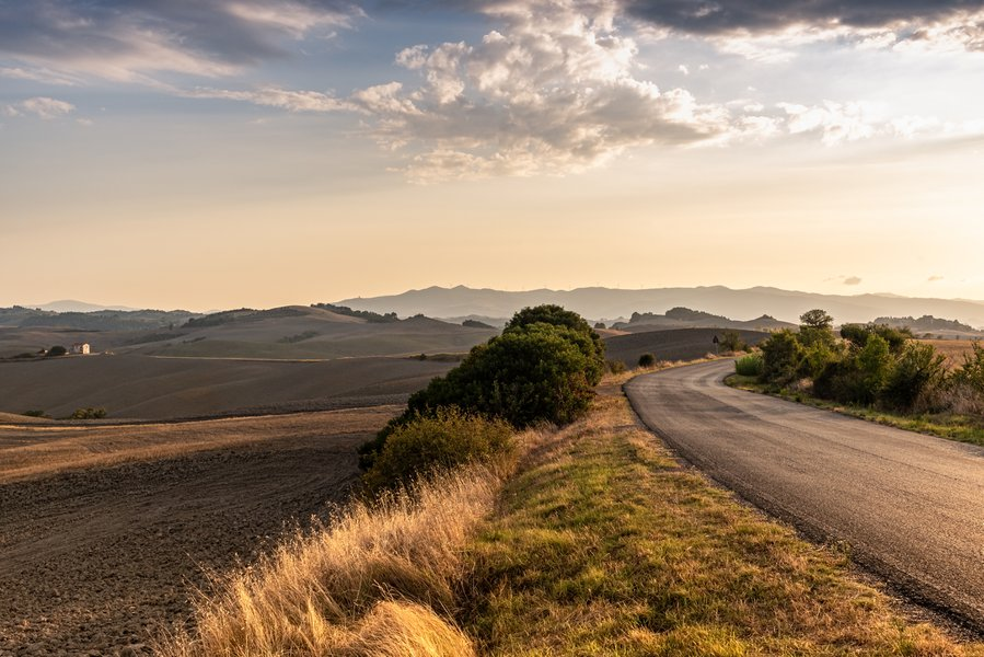 Street with a background of plowed fields in Val d'Orcia