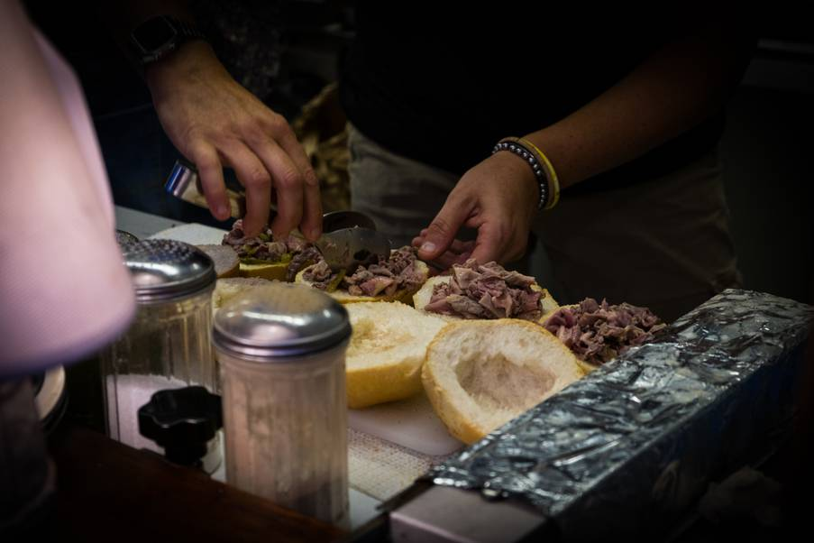 Man putting meat in bread to prepare a lampredotto sandwich