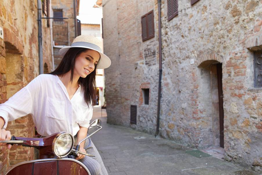 Girl with a straw hat in the narrow streets of an Tuscan town
