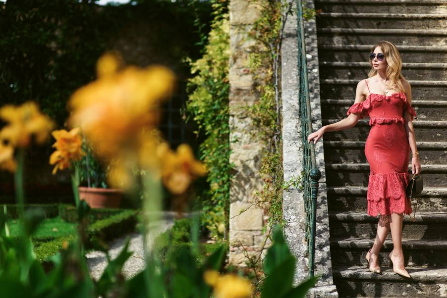 Woman in red dress descending the stairs of an ancient garden in Lucca, Italy